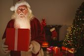 Surprised santa claus delivering a glowing gift at home in the living room
