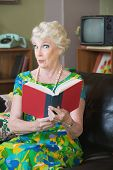 stock photo of tawdry  - Impressed senior woman in 1970s fashion holding book - JPG