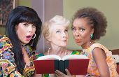 stock photo of tawdry  - Diverse beautiful mature women reading a romance novel - JPG