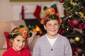 Happy brother and sister in headband near christmas tree at home in the living room
