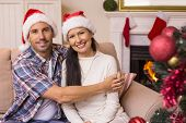 Festive couple hugging on the couch at home in the living room