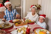 Father in santa hat serving roast turkey at christmas at home in the living room