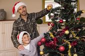 Smiling son and dad decorating the christmas tree at home in the living room