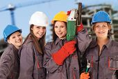 stock photo of work crew  - Four yung women wearing work clothes and helmets isolated with work path in front of a construction background - JPG