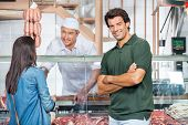 stock photo of slaughterhouse  - Portrait of happy mature man with woman buying meat at butchery - JPG