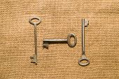 stock photo of hasp  - Three vintage keys to the safe on old cloth - JPG