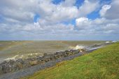 image of dike  - Storm raging over a lake along a dike in spring - JPG
