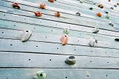 picture of climbing wall  - Grunge surface of an artificial rock climbing wall with toe and hand hold studs - JPG