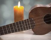 image of ukulele  - An antique soprano Ukulele in still life sits on a marble table with soft lit candle in the background and Bokeh accents - JPG