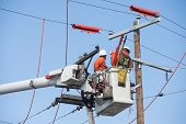 picture of lineman  - Two electric power workers hover in a bucket as they make repairs - JPG