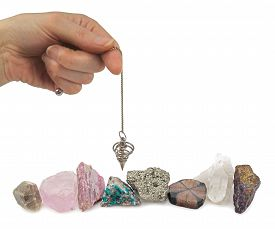 picture of pendulum  - Hand holding a dowsing spiral pendulum over eight different raw mineral specimens on a white background - JPG