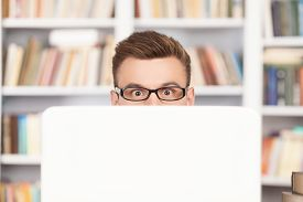 foto of nerd glasses  - Shocked young nerd man in glasses looking out of computer while sitting at the library - JPG