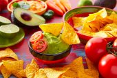 stock photo of nachos  - Mexican food nachos and guacamole with chili peppers and sauces - JPG