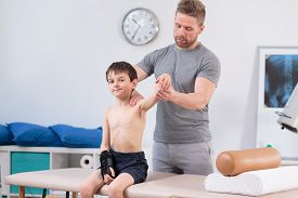 picture of physiotherapist  - Physiotherapist training with little patient after injury - JPG