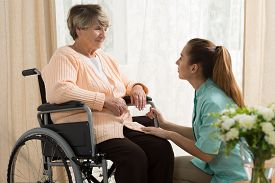 foto of wheelchair  - Picture of caregiver helping old female on wheelchair - JPG