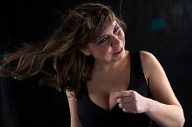 pic of curvy  - Image of curvy woman with flowing hair on black background - JPG