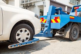 picture of towing  - Tow truck towing a broken down car with focus on car being towed - JPG