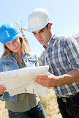 Construction team checking plan on building site