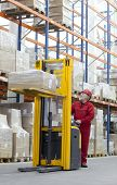 Senior worker manual forklift operator in red uniform at work in warehouse