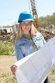 Woman engineer standing on building site with construction plan