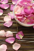 Bowl of rose petals on bamboo spa mats