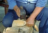 picture of woodcarving  - woodcarver working with an adze to carve a piece of wood - JPG