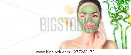 poster of Spa Woman applying Facial green clay Mask. Beauty Treatments. Close-up portrait of beautiful girl ly