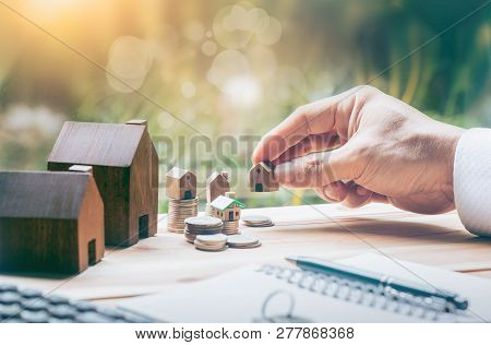 poster of House Placed On Coins Men's Hand Is Planning Savings Money Of Coins To Buy A Home Concept Concept Fo