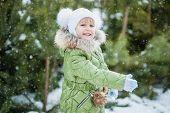 Girl Playing Snowballs. Funny Little Girl Having Fun In Winter Park. Making Snowballs Happy Child Gi poster