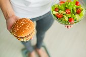 Diet. Woman Measuring Body Weight On Weighing Scale Holding Burger And Salad. Sweets Are Unhealthy J poster