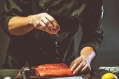 Close Up Chef Putting Salt On Salmon Slice.the Big Salmon Is In The Hands Of The Chef Cook. He Is Us poster