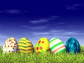 image of easter-eggs  - Various colored easter eggs on grass with some clouds in the background - JPG