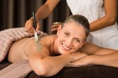 Smiling mature woman looking at camera while beautician getting mud mask on back with brush. Portrai poster
