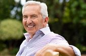 Senior man sitting on a bench at park and looking at camera. Portrait of healthy old man relaxing ou poster