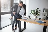 Sexual And Intimate Picture Of Couple At Work. She Sit On Table. He Hold Her Leg In Sexual Pose. The poster