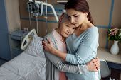 Sad Daughter Hugging Sick Senior Mother With Cancer In Hospital poster