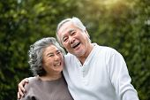 Portrait Of Asian Senior Couple Laughing At The Park. Happy Elderly With Positive Feeling At Outdoor poster