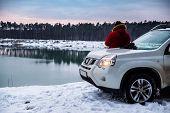 Man Standing Near Suv Car Enjoying View Of Winter Lake. Travel Concept poster