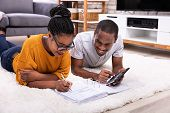 Young African Couple Lying On Carpet Invoice With Calculator poster