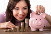 Happy Young Woman Inserting Coin In Piggybank Near Increasing Profit On Desk poster