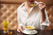 Crop Of Young Female In White Eating Tasty Orange Cream Soup. Woman In Blouse Enjoying Tasty First D poster