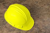 stock photo of osha  - Bright yellow hard hat on a mottled background - JPG