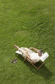 High angle view of middle aged man reading book on deck chair in garden