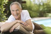 stock photo of recliner  - Cheerful middle aged man reclining on deck chair in garden - JPG