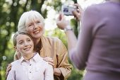 Woman photographing grandmother and granddaughter through digital camera in park