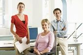 Portrait of middle aged businesswoman with team at office desk