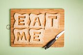 stock photo of eat me  - Eat me text carved out of brown bread slices on wooden chopping board with chef - JPG