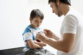 picture of cough syrup  - Father giving son cough syrup at home - JPG