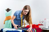 Freelancer - Fashion designer or Tailor working on a design or draft and cutting fabrics with scissors