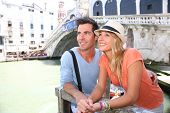 Couple of tourists enjoying view of Canal, Rialto bridge in background